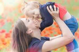 56825048 - mother holding a funny child outdoor at poppy flowers field. happy family values. baby girl and mom. mother's care is most important in baby lfve. mom kissing kid. spring. ?hildren's day, mother's day