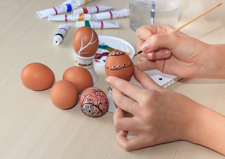 52592141 - female hands painting colorful easter eggs at table, close up