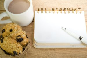 53649616 - blank notebook with coffee and oat cookies on wood background