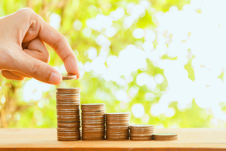 63329993 - hand putting coin on coins stack,savings, finance , business investment growth concept,saving money concept,woman hand putting money coin stack growing business and selective focus.