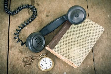 17627849 - vintage phone handset, pocket watches, old book, on wooden table grunge background