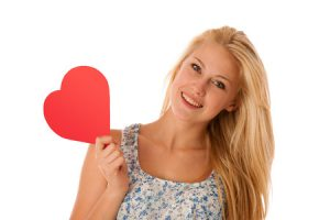 31478611 - beautiful young blonde woman with blue eyes holding red hart banner for valentines day isolated over white