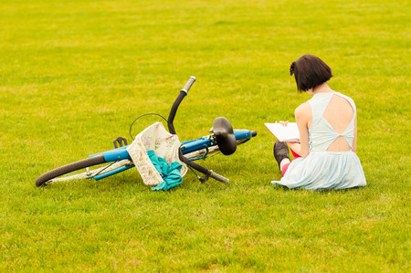 55512178 - beautiful young woman in dress sitting on grass with a book in her hand as back view near vintage bicycle